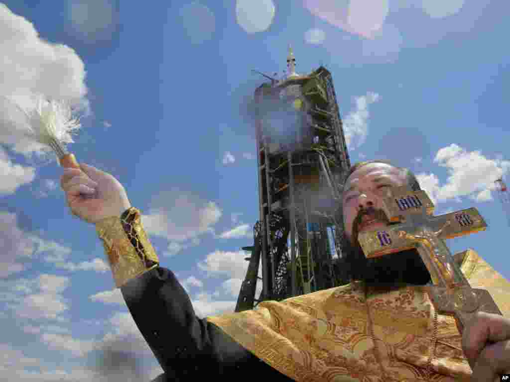 An Orthodox priest blesses the Russian Soyuz rocket that would carry a new crew to the International Space Station, as it awaits launch at the Baikonur cosmodrome in Kazakhstan.Photo by Dmitry Lovetsky for AP