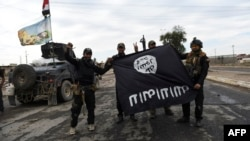 Iraqi soldiers pose with an Islamic State group flag as they hold a position in the village of Gogjali, a few hundred meters from Mosul's eastern edge on November 2.