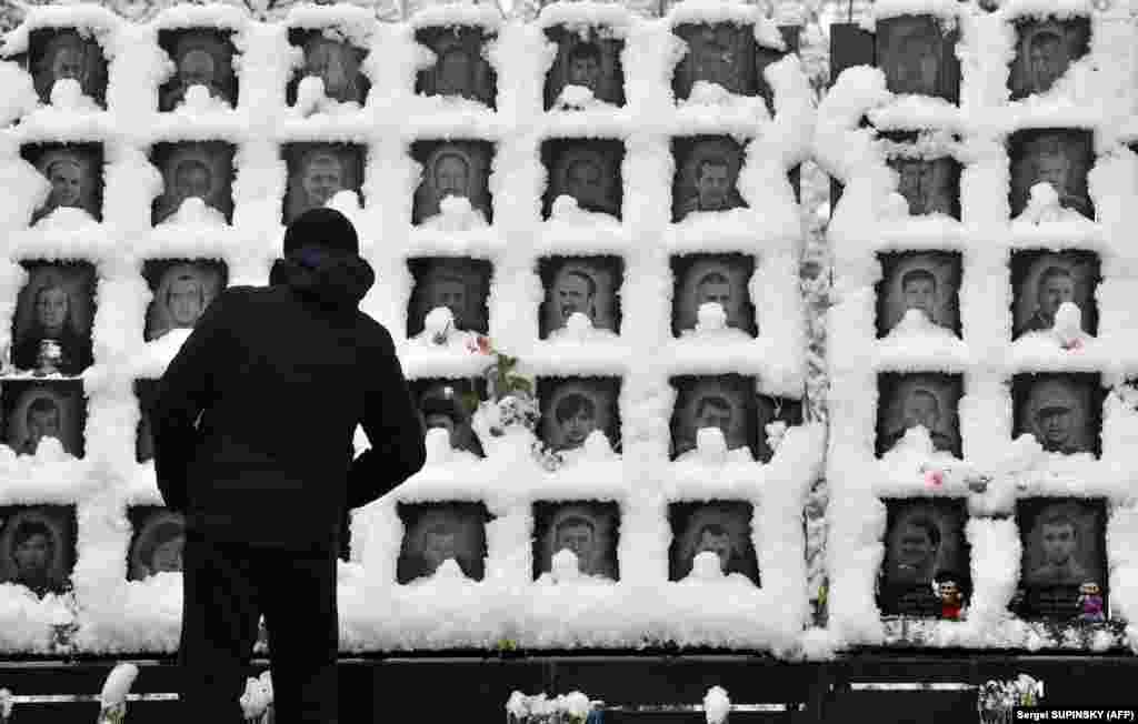 "A man looks at images of the ""Heavenly Hundred"" Memorial commemorating people who died during Ukraine's Maidan protests of 2013-2014, after a heavy snowfall in Kyiv. (AFP/Sergei Supinsky)"