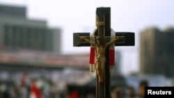 Egypt -- A Christian opposition supporter carries a cross amid the crowd on Tahrir Square in Cairo, 09Feb2011