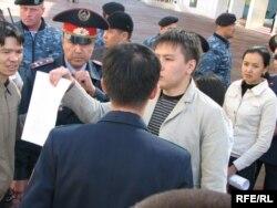 Полицейлер ортасында ҰҚК қызметкерлеріне қарсы хатын көрсетіп тұрған Жанболат Мамай. Астана, 9 қыркүйек 2009 жыл.