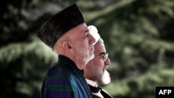 Afghan President Hamid Karzai (left) and Iranian President Hassan Rohani listen to their national anthems during a welcoming ceremony in Tehran in December.