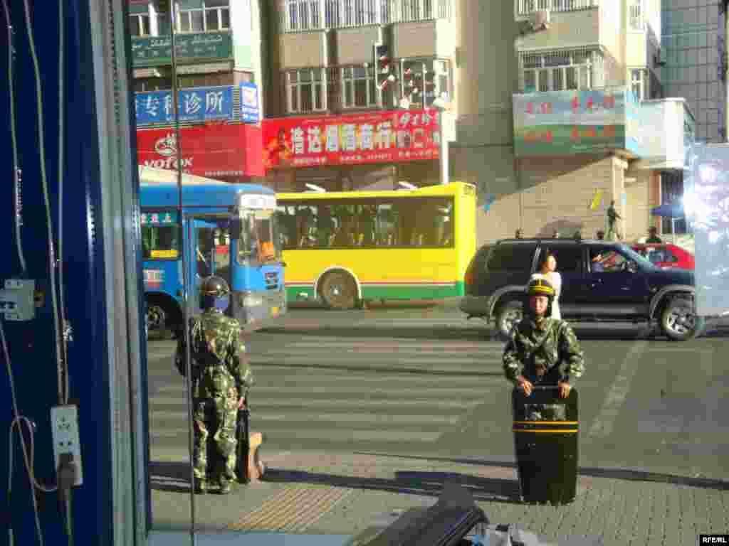 Китайские военные наблюдают за происходящим на улице. Урумчи, 11 июля 2009 года.