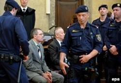 Бывший председатель комитета национальной безопасности Казахстана Альнур Мусаев и бывший помощник Рахата Алиева Вадим Кошляк (слева) под охраной полицейских сидят на скамье подсудимых. Вена, 14 апреля 2015 года.