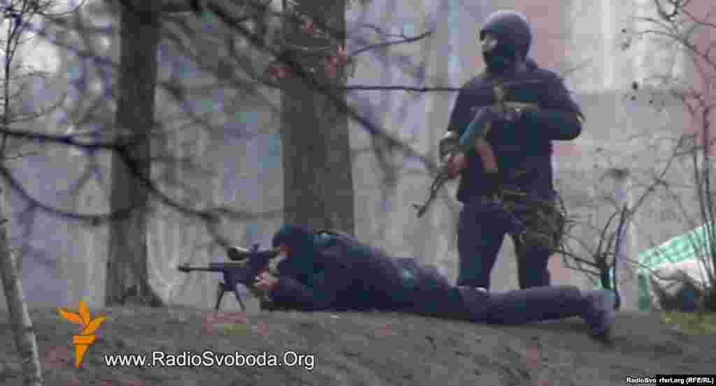 A still photo from a video by RFE/RL's Ukrainian Service shows Ukrainian security personnel with a Kalashnikov assault rifle and sniper rifle in a confrontation with protesters in Kyiv on February 20, 2014. Dozens of protesters are believed to have been killed by gunfire on this day.