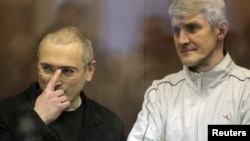 Russia - Jailed Russian former oil tycoon Mikhail Khodorkovsky (L) and his business partner Platon Lebedev stand in the defendants' cage before the start of a court session in Moscow, 29Dec2010