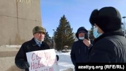 Житель Уральска Бекболат Утепов разговаривает с сотрудником акимата, подошедшим к нему во время проведения одиночного пикета. 26 января 2021 года.