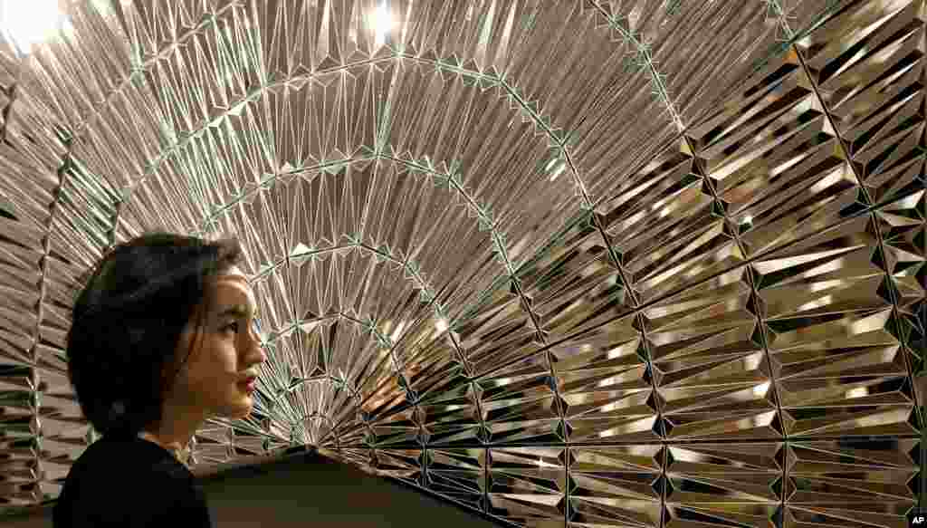 A Sotheby's employee looks towards an artwork by Monir Farmanfarmaian, at Sotheby's auction rooms in London, Friday, April 15, 2016. The painting is expected to realise 80,000-100,000 UK pounds (113,506-141,882 US dollars) when it is auctioned in the firs