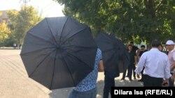 Неизвестные в Шымкенте с зонтами препятствуют репортеру Азаттыка вести съемку. 21 сентября 2019 года.