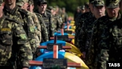 Ukrainian soldiers attend a mass funeral ceremony near Zaporizhzhya on October 1 to bury unidentified members of pro-Ukrainian military forces who were killed in fighting in the country's east.