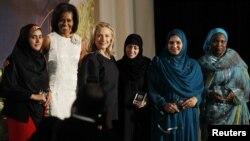 Secretarul de stat Hillary Clinton (a treia din stânga) şi prima doamnă Michelle Obama (a doua din stânga) cu patru dintre cele 10 femei premiate de Departamentul de Stat, 8 martie 2012