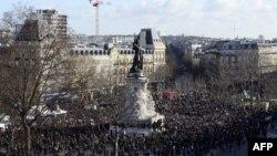 Люди на площади Республики в Париже, собравшиеся на марш в память о жертвах атак. 11 января 2015 года.