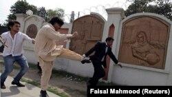 A supporter of former Pakistani President Pervez Musharraf kicks an anti-Musharraf lawyer outside a court in Rawalpindi on April 23.