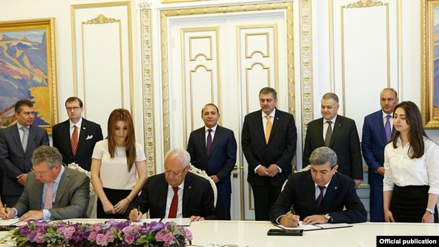 Armenia - Energy Minister Yervand Zakharian (C) and Joseph Brandt (L), the CEO of the U.S company ContourGlobal, sign a deal on the sale of Vorotan Hydro Cascade, Yerevan, 8Jun2015.