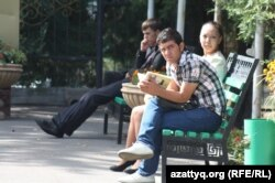 Университет ауласында отырған студенттер. (Көрнекі сурет)