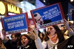 """Студенты перед зданием банка Halkbank держат плакаты и выкрикивают: """"АКР грабит народ"""". 19 декабря 2013 года."""
