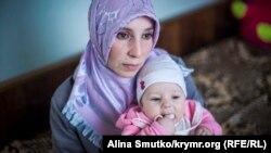 Алиме Абдуллаева держит на руках дочь Асму