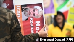 A protester holds a placard with a crossed-out portrait of Iranian President Hassan Rouhani during a demonstration in support of the Iranian people amid a wave of protests spreading throughout Iran, on January 3, 2018, in Brussels.