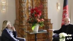 د افغانستان ولسمشر حامد کرزی او د امریکا د بهرنیو چارو وزیره هیلري کلینټن د بون غونډې ته په څنګ سره ویني.۵ ډسمبر ۲۰۱۱م کال
