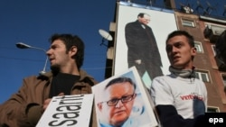 Косовские албанцы заранее протестуют против будущих предложений Ахтисаари (на плакате внизу) по статусу края