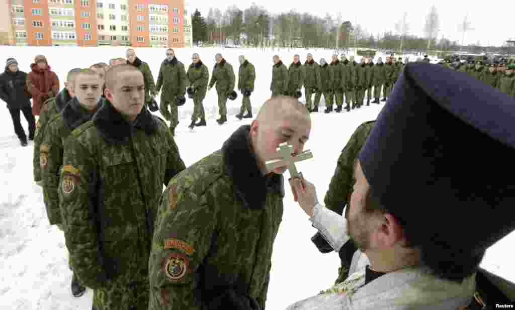 Belarusian Interior Ministry troops line up to kiss an Orthodox cross after a service at a military base in Minsk. (REUTERS/Vasily Fedosenko)