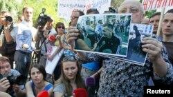 Учасники акції під МВС тримають фото підозрюваних у побитті журналістів 18 травня у Києві