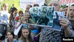 Учасники мітингу під МВС тримають фото ймовірних нападників на журналістів 18 травня в Києві, 20 травня 2013 року