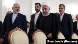 Iranian President Hassan Rohani (center right) walks with Iranian Foreign Minister Mohammad Javad Zarif (left).