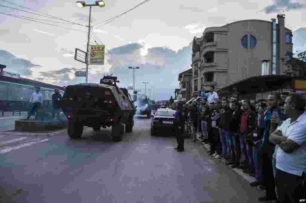 People watch as Macedonian police troops in armored vehicles leave the area where fighting took place in Kumanovo.