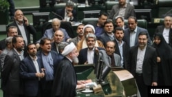 Iranian President Hassan Rohani (center) presents his budget bill to the country's parliament on December 25.