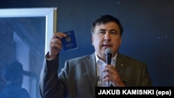 Міхэіл Саакашвілі паказвае журналістам у Варшаве свой украінскі пашпарт 6 жніўня 2017 году