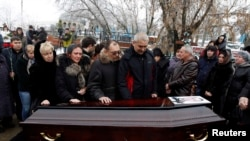 Relatives and other mourners gathered around the coffin at the funeral in Volgograd on December 31 to bury the first of the dozens killed on December 29 and 30.