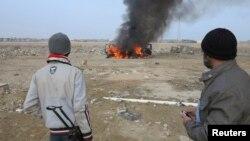 Вооруженные сунниты наблюдают за горящей полицейской машиной. 2 января 2014 года.