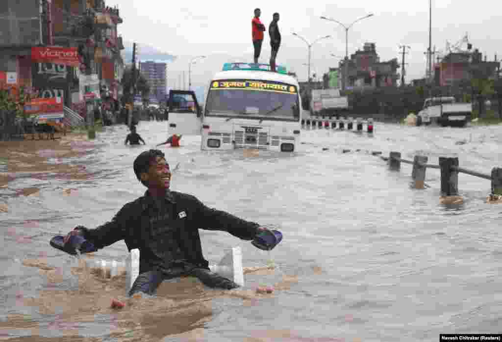 A boy smiles as he uses an improvised raft to maneuver through floodwater in Bhaktapur, Nepal. (Reuters/Navesh Chitrakar)