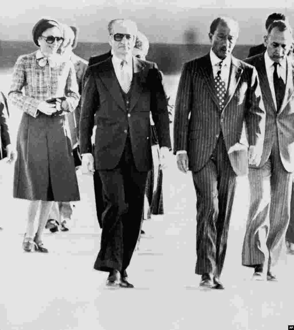 Iran's monarch, Shah Mohammad Reza Pahlavi, leaves his country for the last time on January 16, 1979, going first to Egypt. He and his wife, Empress Farah, were greeted by President Anwar Sadat (second from right). Iranian students were angry that U.S. President Jimmy Carter later allowed the shah to travel to New York for cancer treatment. The shah had fled Tehran amid a surge of demonstrations against his rule. His troops had answered some of them with deadly gunfire.