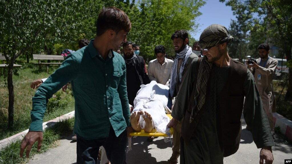 Afghan volunteers bring the body of a resident killed in a car-bomb attack to the Wazir Akbar Khan hospital in Kabul on May 31.