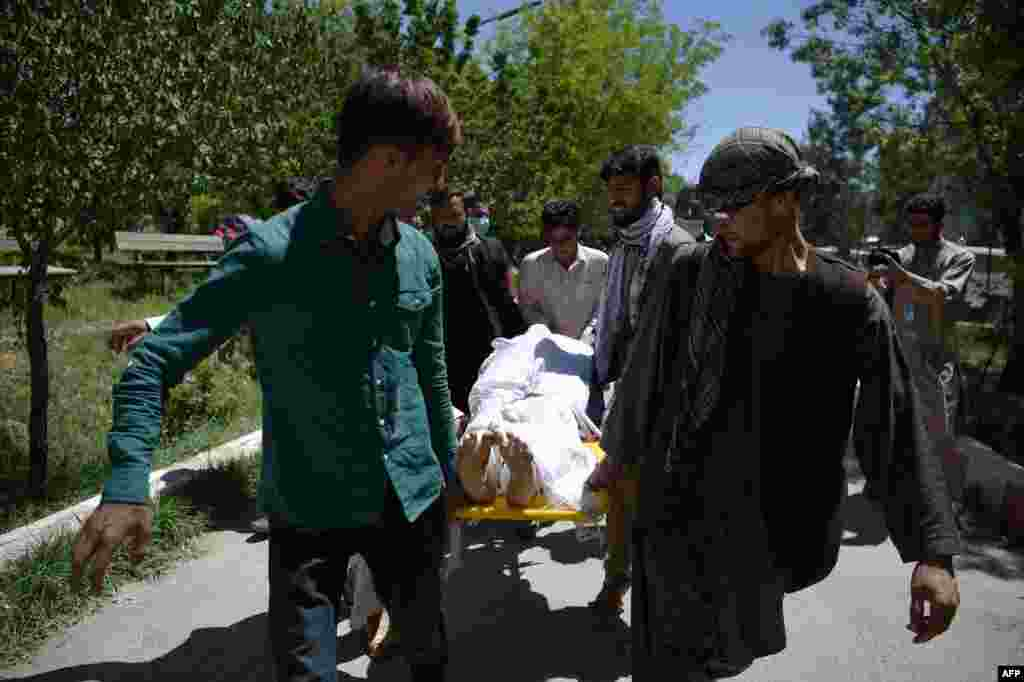 Afghan volunteers bring the body of a resident killed in the attack to the Wazir Akbar Khan hospital.