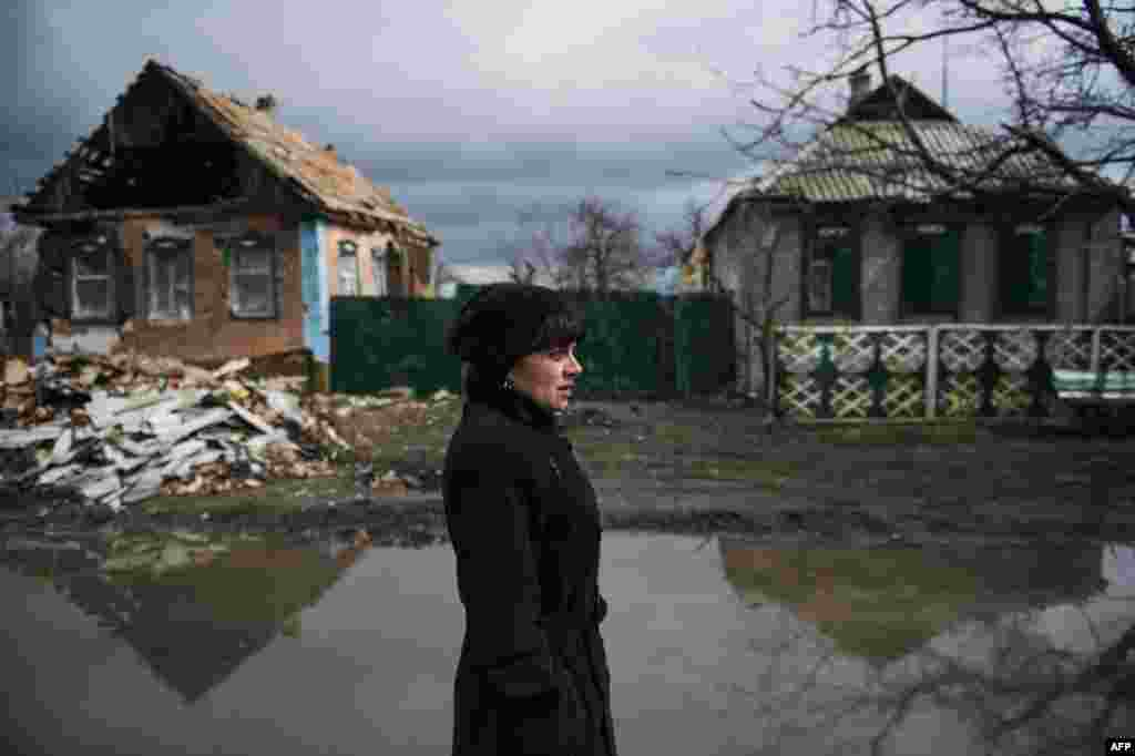 A woman stands outside her destroyed home as she speaks to neighbors in the village of Nikishino, eastern Ukraine on April 21. (AFP/Odd Anderson)