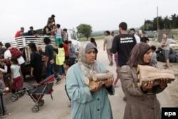 Беженки из лагеря Идомени несут дрова для отопления и разогрева пищи