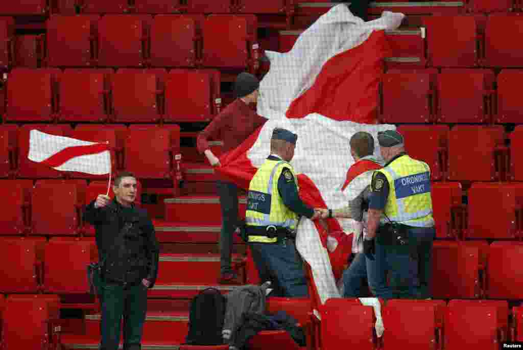 Security personnel stop a fan of Belarus from displaying a former Belarusian flag that the current government has outlawed at a 2013 world ice hockey championship match against Slovenia at the Globe Arena in Stockholm. (Reuters/Arnd Wiegmann)
