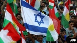 Iraqi Kurds fly an Israeli flag and Kurdish flags during an event to urge people to vote in the upcoming independence referendum in Arbil, the capital of the autonomous Kurdish region of northern Iraq.