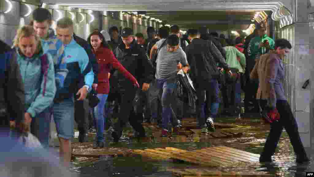 People walk on wooden boards inside a flooded underground pedestrian subway in Moscow. (AFP/Vasily Maksimov)
