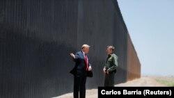 Трамп Мексика билан чегарада қурилаётган девор олдида.