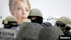Қорғаныс құралдарын ұстаған наразылар Украинаның бұрынғы премьер-министрі Юлия Тимошенконың баннерінің қасында тұр. Киев, 8 ақпан 2014 жыл.