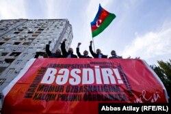 """На трибуне митинга НСДС против фальсфикации президентских выборов. Белаю надпись на красном фоне гласит """"Хватит!"""""""