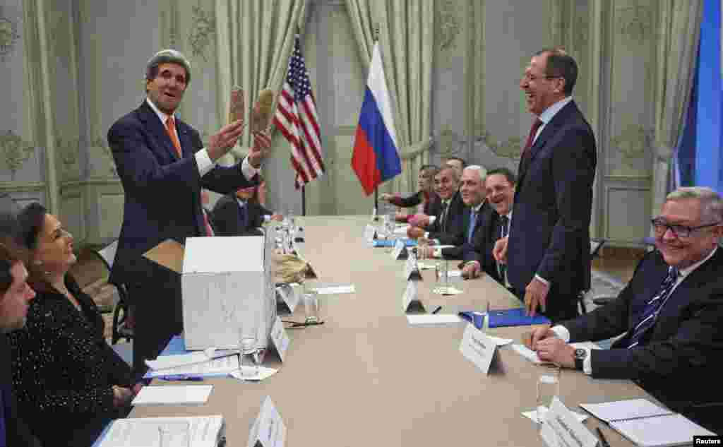 U.S, Secretary of State John Kerry (standing, left) holds up a pair of Idaho potatoes as a gift for Russian Foreign Minister Sergei Lavrov (standing, right) at the start of their meeting at the U.S. Ambassador's residence in Paris on January 13. (Reuters/Pablo Martinez Monsivais)