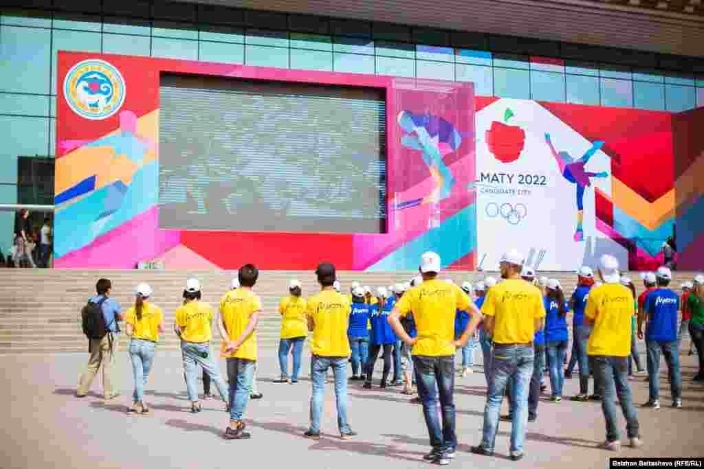 Волонтеры смотрят с телеэкрана рекламный ролик о готовности Алматы принять зимнюю Олимпиаду 2022 года.