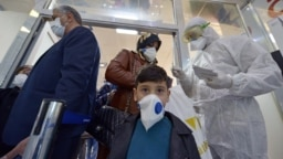 پرسنل بهداشتی در حال پخش برگههای اطلاعاتی بین مسافرانی که از ایران وارد نجف در عراق شدهاند