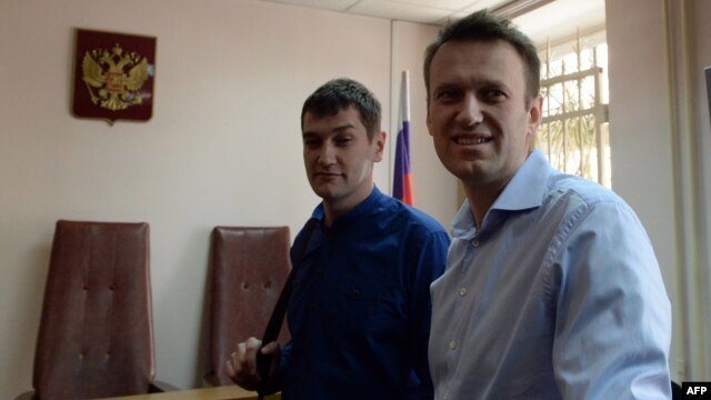 Kremlin critic and opposition leader Aleksei Navalny (right) and his brother Oleg stand in a courtroom in Moscow on April 24.