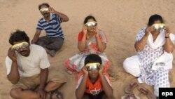 Туристи спостерігають часткове сонячне затемнення на пляжі в південному індійському місті Ченнаі